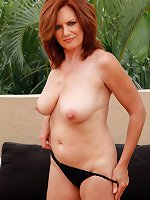 Busty mature redhead Andi James gets butt naked on the roof.